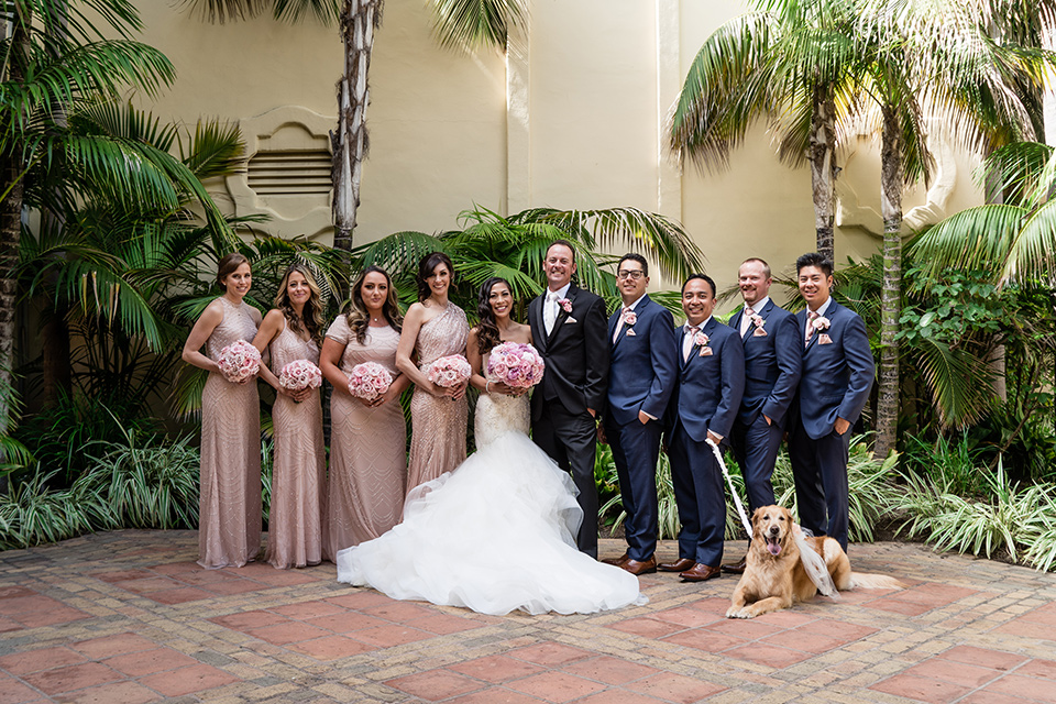 The bride in a mermaid style gown with a sweetheart neckline and the groom in a black tuxedo with a white long tie, the bridesmaids are in rose gold blush gowns and the groomsmen in navy blue suits with blush bow ties