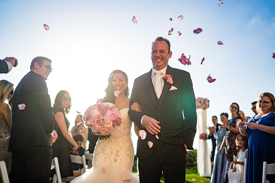 The bride in a mermaid style gown with a sweetheart neckline and the groom in a black tuxedo with a white long tie walking down the aisle