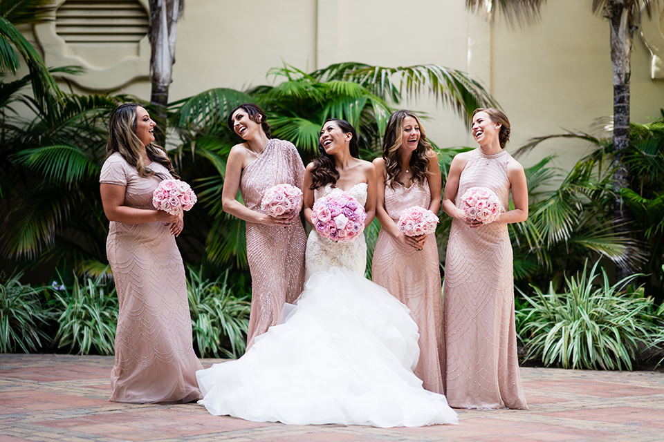 The bride in a mermaid style gown with a sweetheart neckline the bridesmaids are in rose gold blush gowns