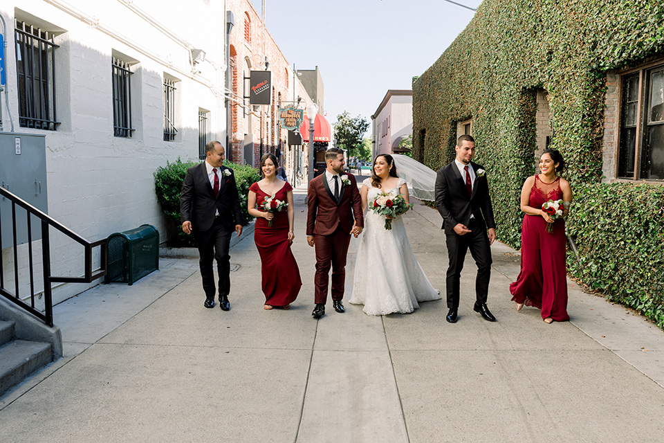 the bride in a lace a line gown with tulle cap sleeves and a modified sweetheart neckline, the groom in burgundy tuxedo with a shawl lapel tuxedo with a black long tie.  The groomsmen in black and grey suits with burgundy long tie and the bridesmaids in wine and burgundy long gowns