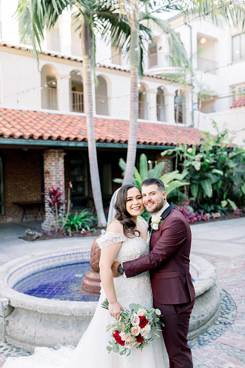 the bride in a lace a line gown with tulle cap sleeves and a modified sweetheart neckline, the groom in burgundy tuxedo with a shawl lapel tuxedo with a black long tie hugging by fountain