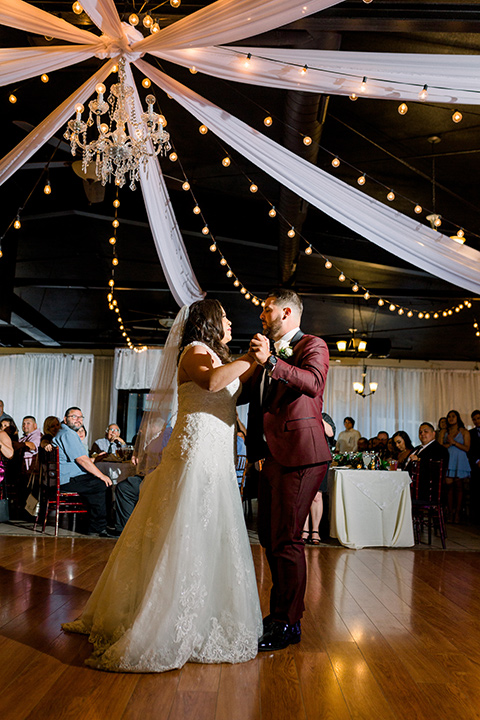 the bride in a lace a line gown with tulle cap sleeves and a modified sweetheart neckline, the groom in burgundy tuxedo with a shawl lapel tuxedo with a black long tie dancing the first dance