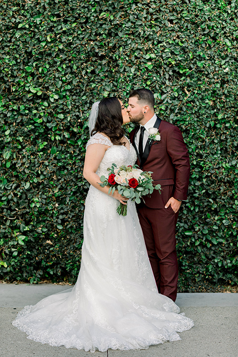 the bride in a lace a line gown with tulle cap sleeves and a modified sweetheart neckline, the groom in burgundy tuxedo with a shawl lapel tuxedo with a black long tie kissing by ivy wall