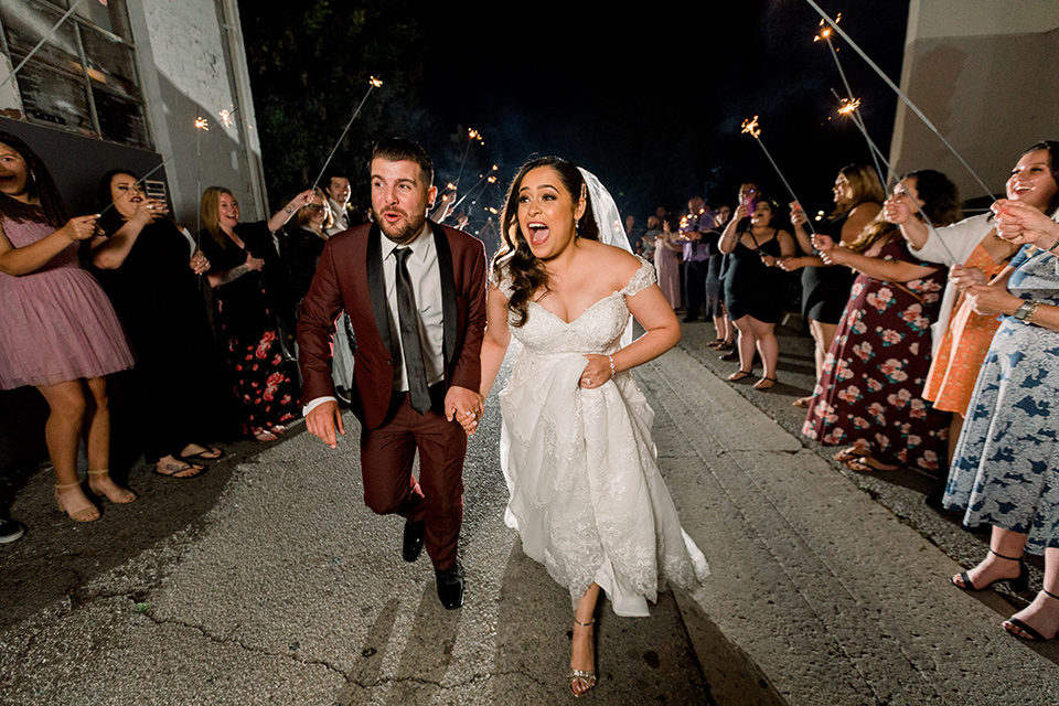 the bride in a lace a line gown with tulle cap sleeves and a modified sweetheart neckline, the groom in burgundy tuxedo with a shawl lapel tuxedo with a black long tie smiling and leaving the wedding with the guests holding sparklers