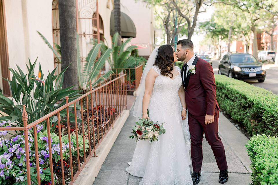 the bride in a lace a line gown with tulle cap sleeves and a modified sweetheart neckline, the groom in burgundy tuxedo with a shawl lapel tuxedo with a black long tie kissing outside the venue