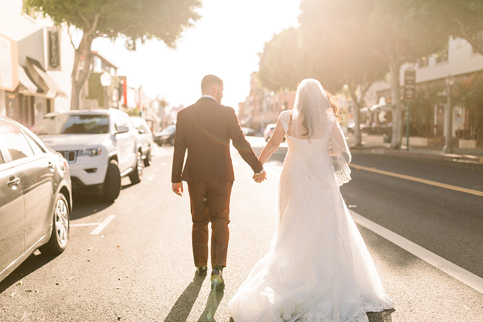 the bride in a lace a line gown with tulle cap sleeves and a modified sweetheart neckline, the groom in burgundy tuxedo with a shawl lapel tuxedo with a black long tie walking away from the camera down the street