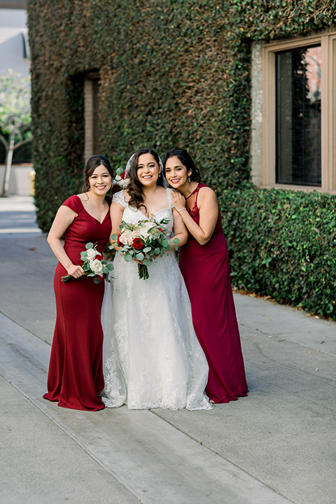 the bride in a lace a line gown with tulle cap sleeves and a modified sweetheart neckline and the bridesmaids in wine and burgundy long gowns