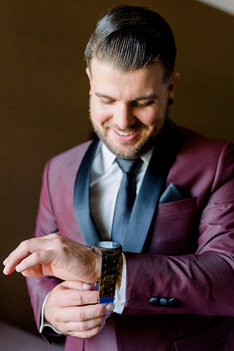 the groom in burgundy tuxedo with a shawl lapel tuxedo with a black long tie looking at watch