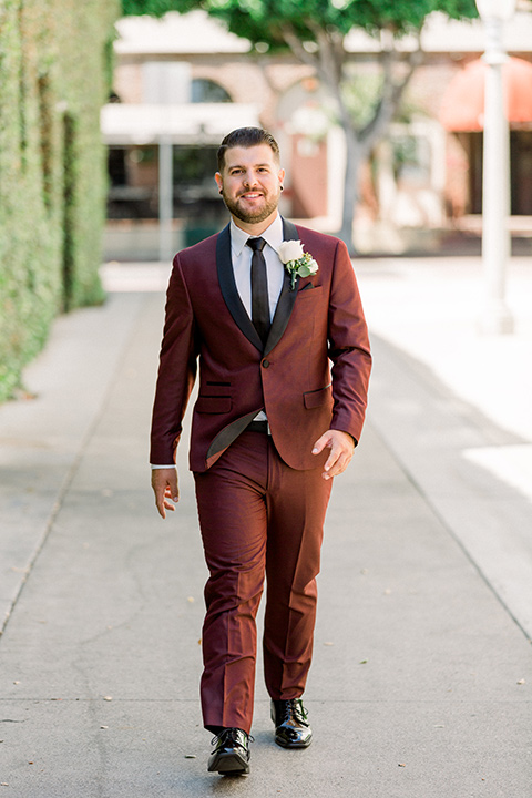 the groom in burgundy tuxedo with a shawl lapel tuxedo with a black long walking towards camera