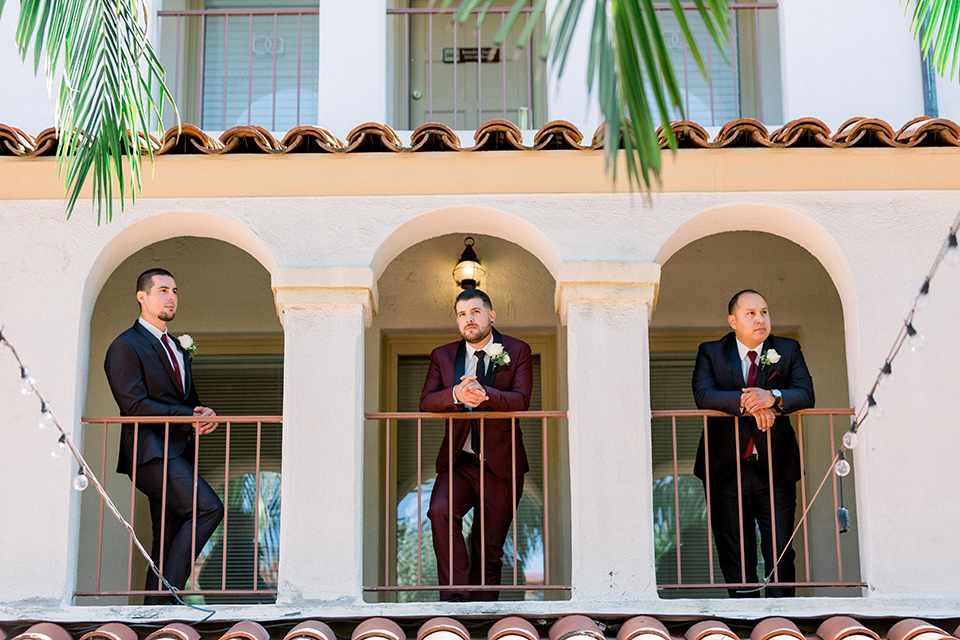 the groom in burgundy tuxedo with a shawl lapel tuxedo with a black long tie, The groomsmen in black and grey suits with burgundy long ties