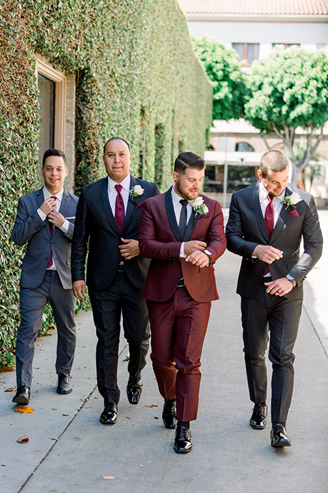 the groom in burgundy tuxedo with a shawl lapel tuxedo with a black long tie and groomsmen in black and grey suits with long burgundy ties walking towards camera