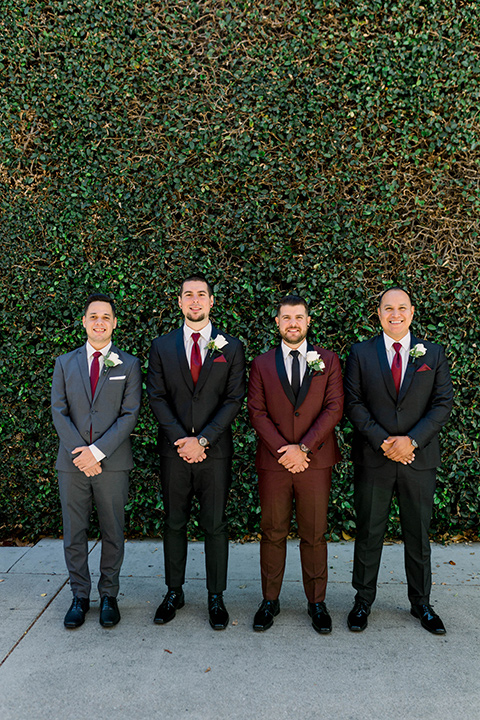 the groom in burgundy tuxedo with a shawl lapel tuxedo with a black long tie and his groomsmen in black and grey suits with burgundy long ties