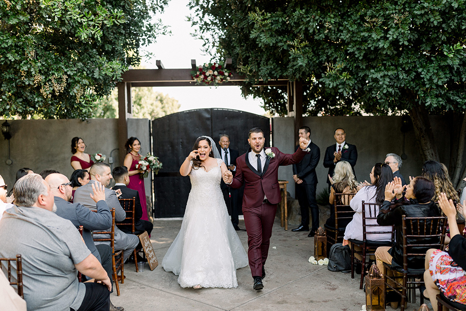 the bride in a lace a line gown with tulle cap sleeves and a modified sweetheart neckline, the groom in burgundy tuxedo with a shawl lapel tuxedo with a black long tie at the ceremony