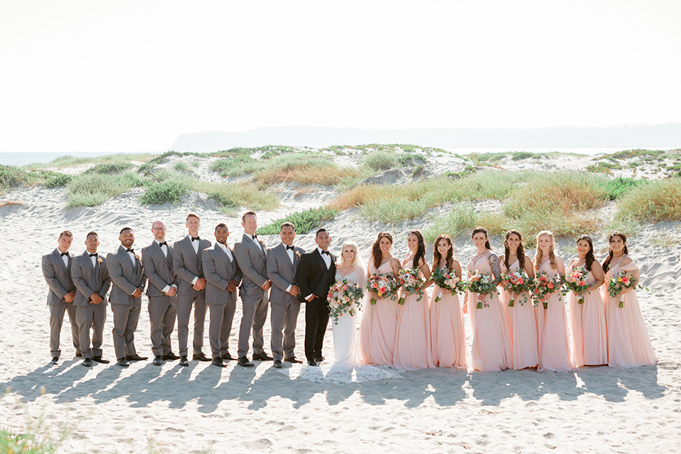 bride in a lace formfitting gown and a long veil, the groom in a black tuxedo with a black bow tie, the bridesmaids in blush pink gowns, and the groomsmen in light grey suits with black bow ties