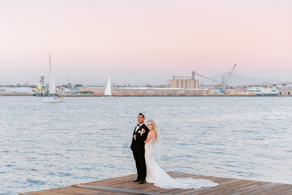 bride in a lace formfitting gown and a long veil, the groom in a black tuxedo with a black bow tie standing on the dock with the ocean and city behind them