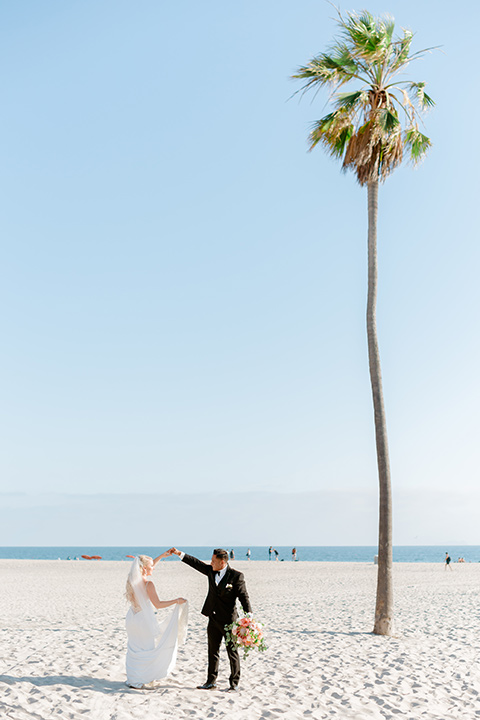 bride in a lace formfitting gown and a long veil, the groom in a black tuxedo with a black bow tie