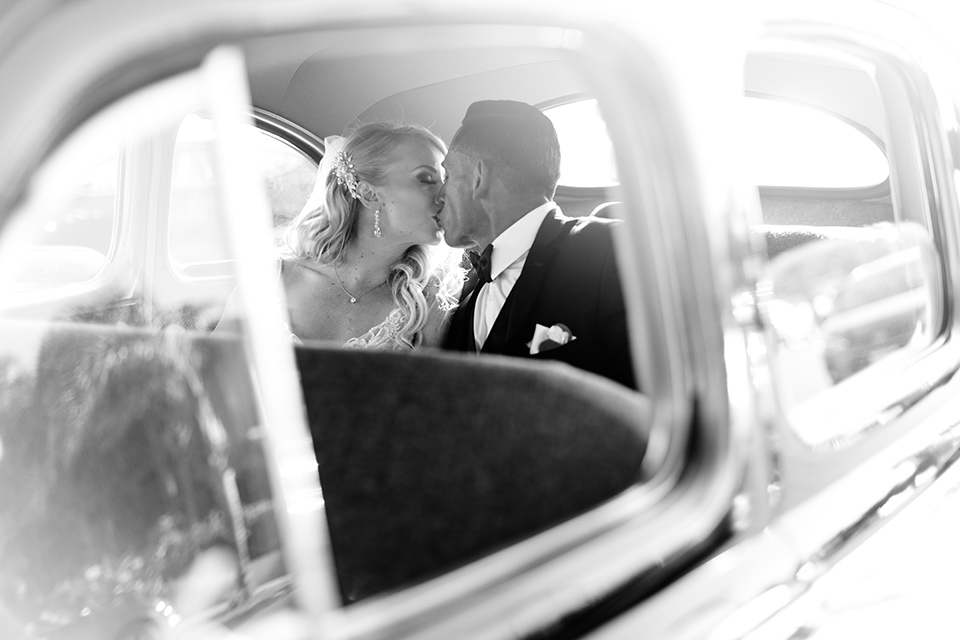 bride in a lace formfitting gown and a long veil, the groom in a black tuxedo with a black bow tie sitting in the back of a vintage police car
