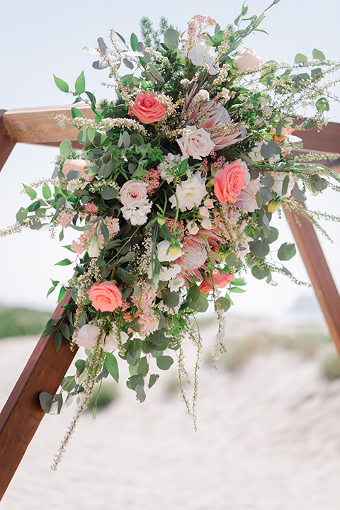pink and green florals with a wooden geometric arch