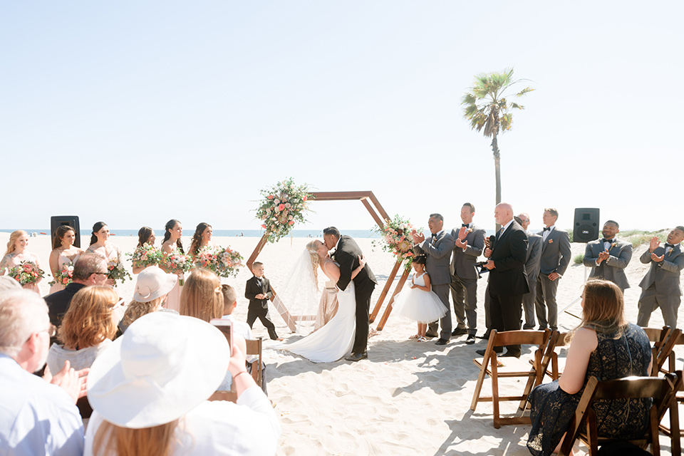 bride in a lace formfitting gown and a long veil, the groom in a black tuxedo with a black bow tie, the bridesmaids in blush pink gowns, and the groomsmen in light grey suits with black bow ties with the ceremony on the sand