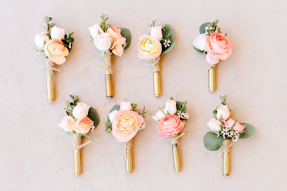 pink and white boutonnières with gold trimming