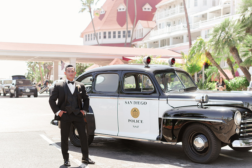 the groom in a black tuxedo with a black bow tie standing in front of the vintage police car