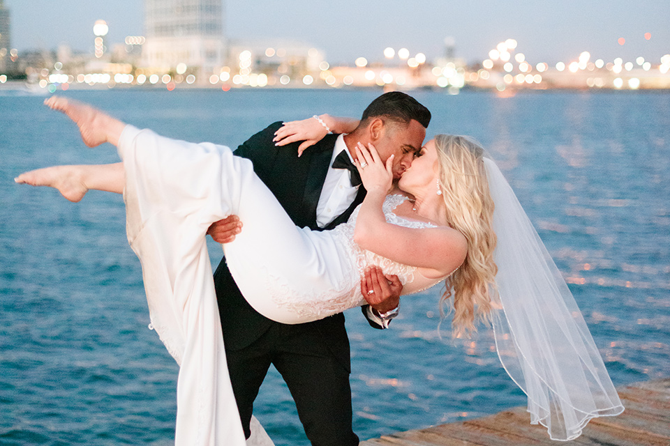 bride in a lace formfitting gown and a long veil, the groom in a black tuxedo with a black bow tie groom dipping bride
