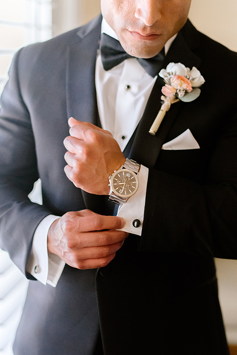 the groom in a black tuxedo and black bow tie