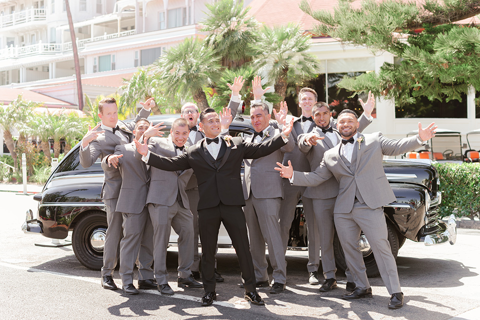 the groom in a black tuxedo with a black bow tie and the groomsmen in light grey suits with black bow ties laughing