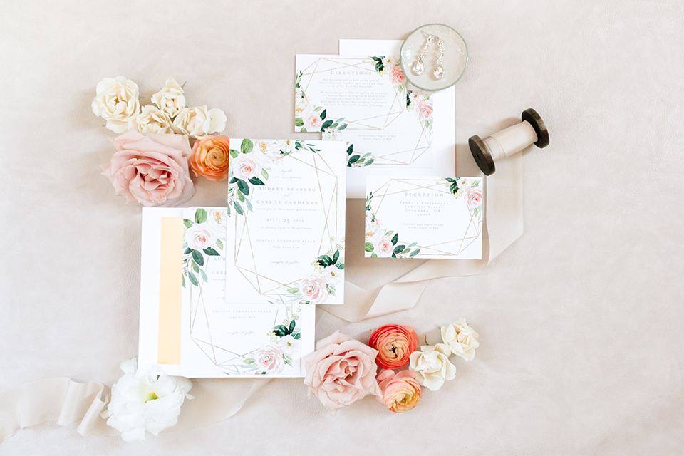 white invitations with a green and pink floral design