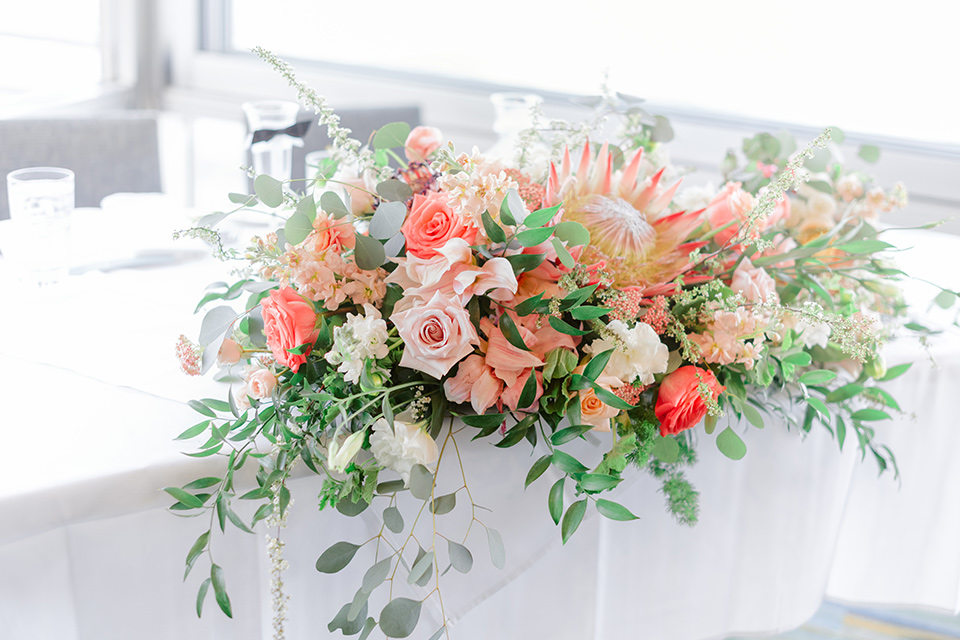 pink green and white flowers on the wedding reception tables