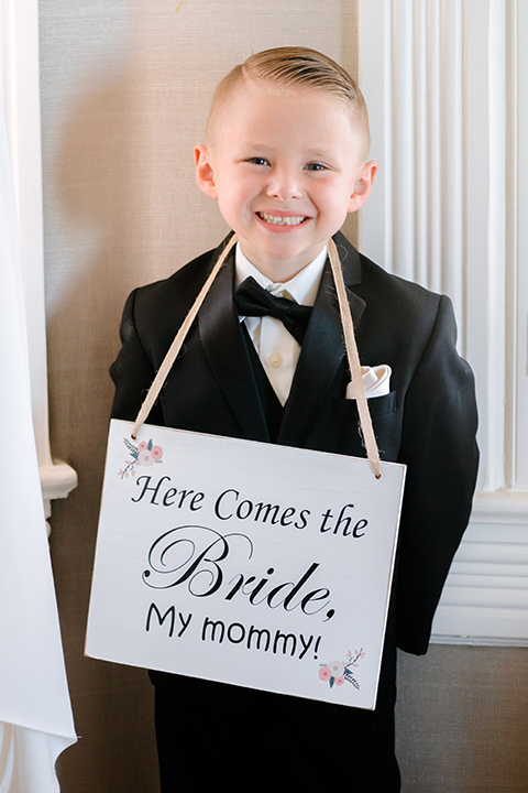 the ringbearer in a black tuxedo holding a sign