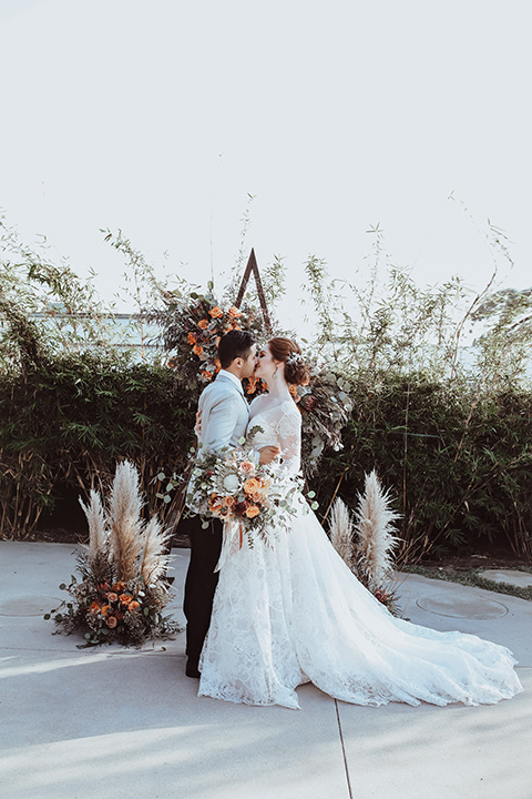 the bride is in a white flowing gown with a lace sleeves and a high neck line, and the groom in a grey jacket with black pants