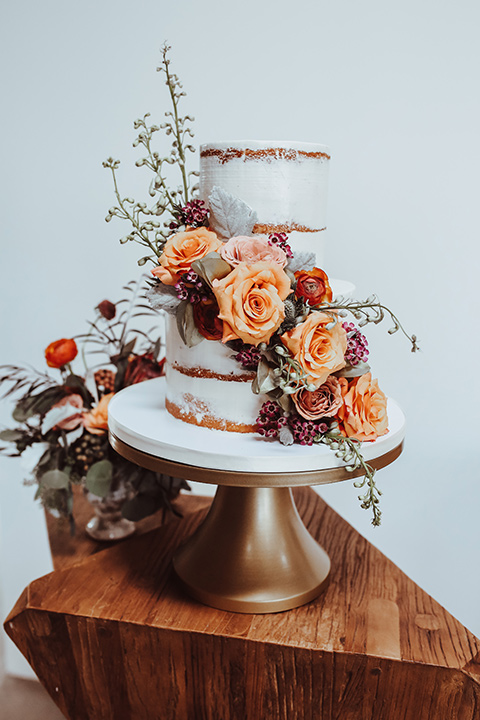 a white natural frosted cake with orange and green flowers