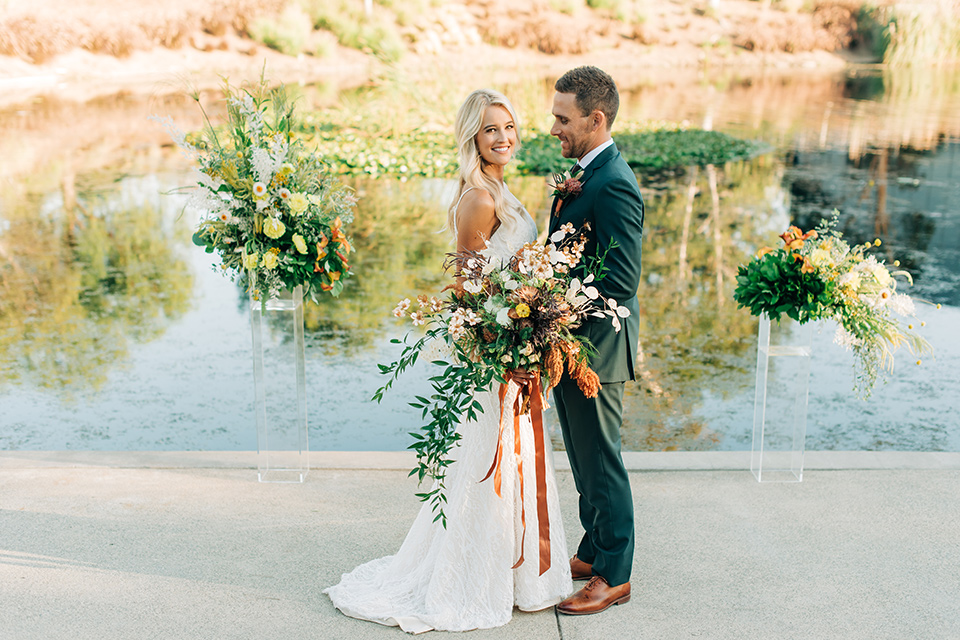 bride in a white lace bohemian style wedding gown with a tan wide brimmed hat and the groom in a dark green suit with a chocolate long tie