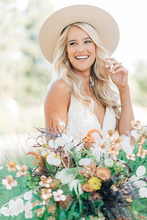 bride in a white lace bohemian style wedding gown with a tan wide brimmed hat