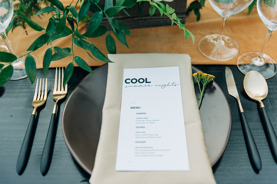 black table linens with modern gold flatware