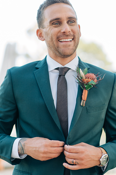 the groom in a dark green suit with a chocolate long tie