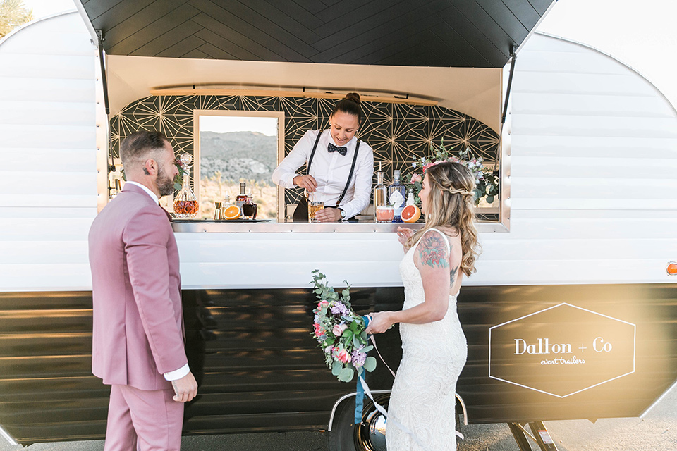 bride in a white lace bohemian style gown with a sweetheart neckline and thin straps and the groom in a rose pink suit with a burgundy bow tie at bar cart