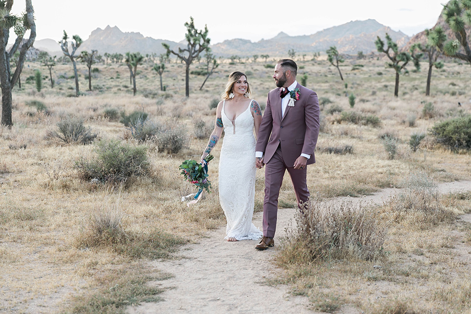 bride in a white lace bohemian style gown with a sweetheart neckline and thin straps and the groom in a rose pink suit with a burgundy bow tie walking together