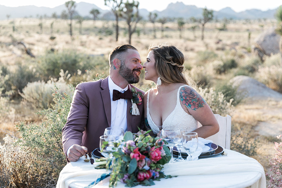 bride in a white lace bohemian style gown with a sweetheart neckline and thin straps and the groom in a rose pink suit with a burgundy bow tie sitting at sweetheart table