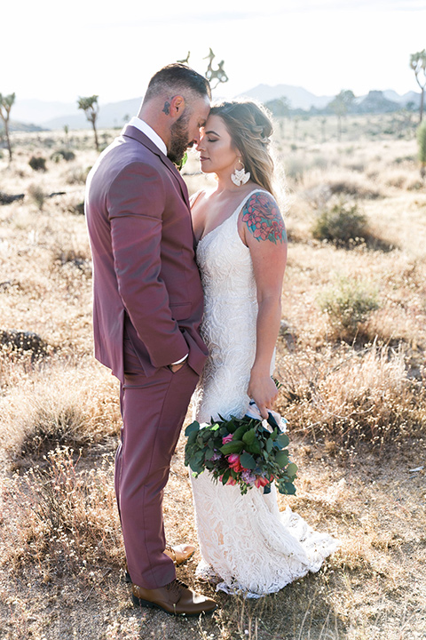 bride in a white lace bohemian style gown with a sweetheart neckline and thin straps and the groom in a rose pink suit with a burgundy bow tie
