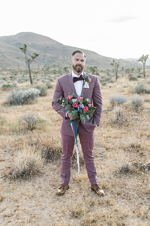 groom in a rose pink suit with a burgundy bow tie