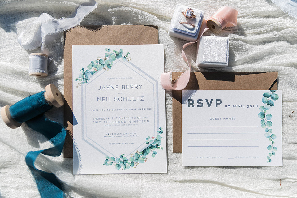 white invitations with sage details