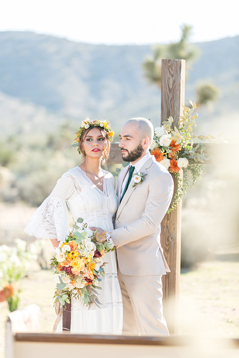 bride in a bohemian style gown with lace and a floral crown, the groom in a tan suit with a teal long tie