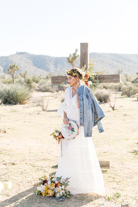 bride in a bohemian style gown with lace and a floral crown and a jean jacket