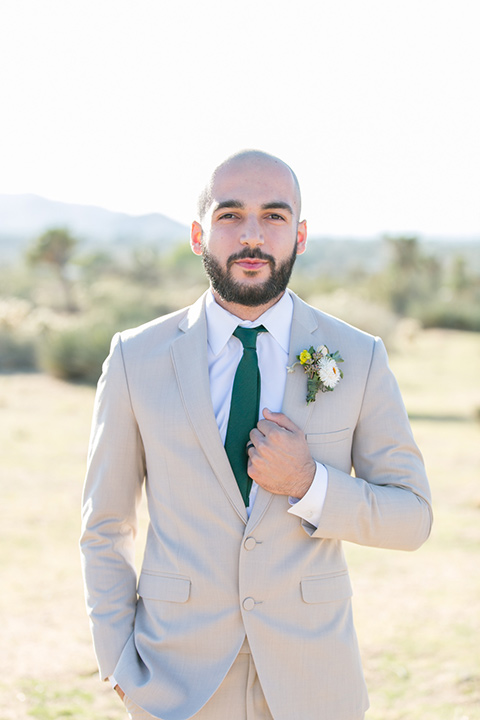 groom in a tan notch lapel with a teal long tie