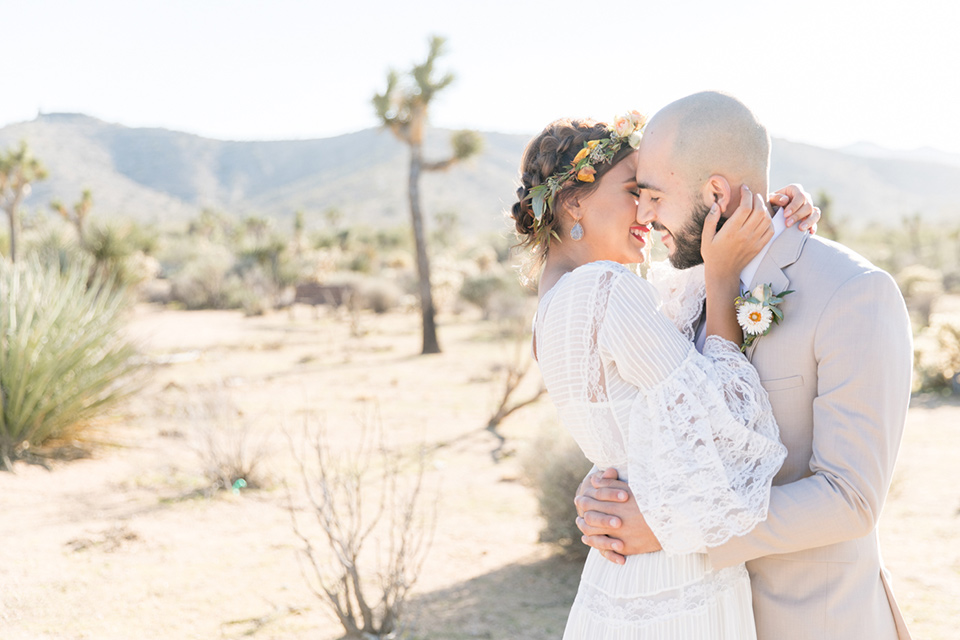 bride in a bohemian style gown with lace and a floral crown, the groom in a tan suit with a teal long tie kissing