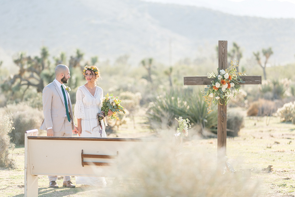 bride in a bohemian style gown with lace and a floral crown, the groom in a tan suit with a teal long tie walking