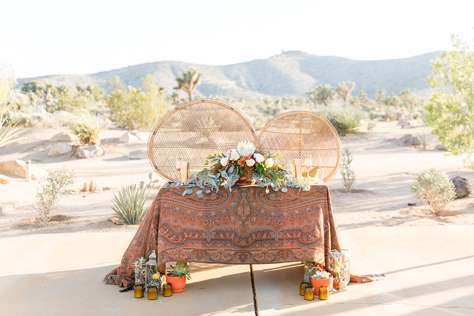 bohemian sweetheart table with wicker chairs and bohemian florals