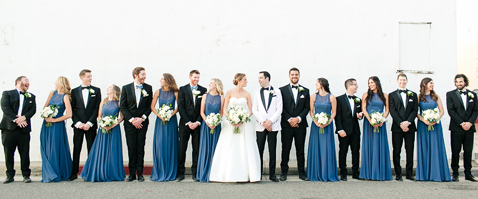 dusty-blue-bridesmaids-gowns-with-the-groomsmen-in-black-tuxedos